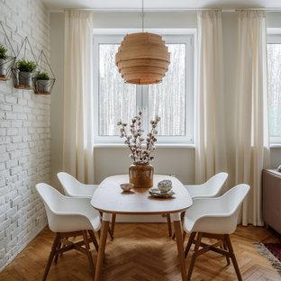 Cette image montre une salle à manger nordique avec un mur blanc, un sol en bois brun, un sol marron et un mur en parement de brique.