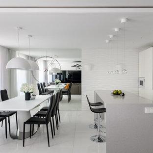 Стильный дизайн: большая кухня-столовая в современном стиле с белыми стенами и белым полом - последний тренд