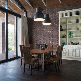 Foto di un'ampia sala da pranzo aperta verso la cucina minimal con pareti marroni, pavimento in laminato, pavimento marrone, camino bifacciale e cornice del camino in mattoni