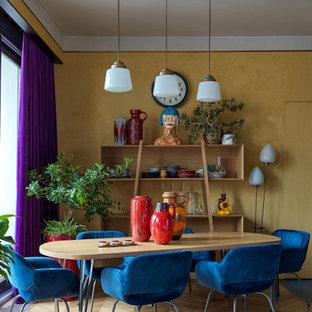 Стильный дизайн: гостиная-столовая в стиле фьюжн с желтыми стенами, паркетным полом среднего тона и коричневым полом - последний тренд