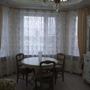Ispirazione per una sala da pranzo aperta verso il soggiorno country di medie dimensioni con pareti beige, pavimento in laminato e nessun camino