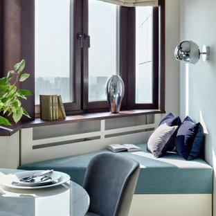 На фото: столовая среднего размера в современном стиле с белыми стенами и белым полом
