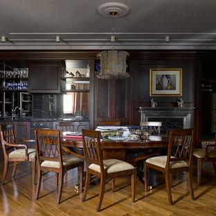 Неиссякаемый источник вдохновения для домашнего уюта: столовая в классическом стиле с коричневыми стенами, паркетным полом среднего тона, стандартным камином и коричневым полом
