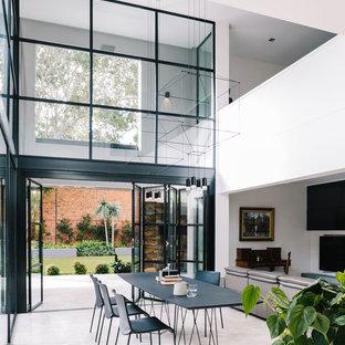 На фото: гостиная-столовая в современном стиле с белыми стенами и белым полом с