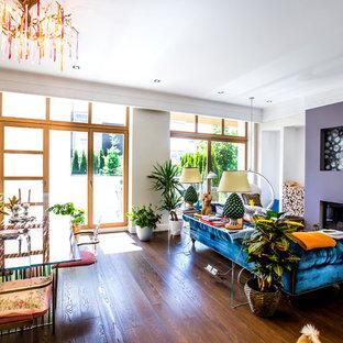 На фото: гостиные-столовые в стиле фьюжн с коричневым полом, бежевыми стенами, темным паркетным полом и стандартным камином