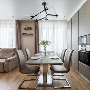 На фото: гостиные-столовые в современном стиле с бежевыми стенами, коричневым полом и паркетным полом среднего тона