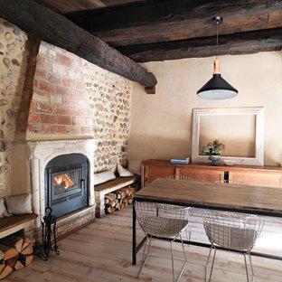 Diseño de comedor rural con paredes beige, suelo de madera clara, chimenea tradicional y marco de chimenea de ladrillo