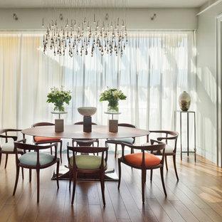 На фото: отдельные столовые в современном стиле с серыми стенами, паркетным полом среднего тона и оранжевым полом