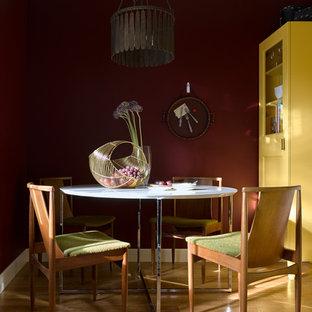 Пример оригинального дизайна интерьера: столовая в стиле современная классика с красными стенами и паркетным полом среднего тона без камина
