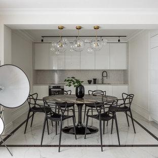 На фото: кухня-столовая в стиле фьюжн с белыми стенами и белым полом с