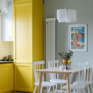На фото: кухня-столовая в стиле современная классика с зелеными стенами, светлым паркетным полом и бежевым полом