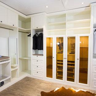 Foto di un grande spazio per vestirsi unisex tradizionale con ante con bugna sagomata, ante bianche, pavimento in compensato e pavimento marrone