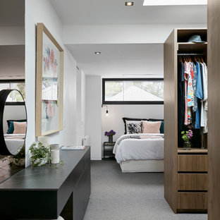 Photo of a contemporary women's dressing room in Melbourne with open cabinets, medium wood cabinets, carpet and grey floor.