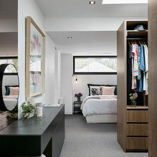 Imagen de vestidor de mujer, actual, con armarios abiertos, puertas de armario de madera oscura, moqueta y suelo gris