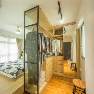 Foto di una cabina armadio unisex contemporanea con nessun'anta, ante in legno chiaro e pavimento in legno massello medio
