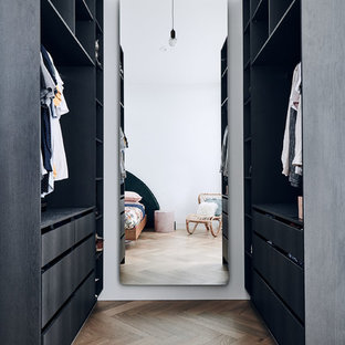 Inspiration for a contemporary walk-in wardrobe in Melbourne with flat-panel cabinets, black cabinets, medium hardwood floors and brown floor.