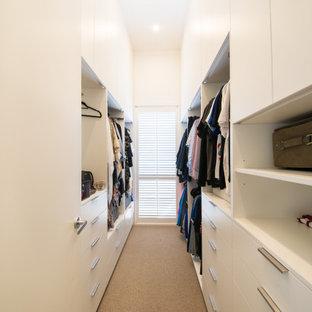 Esempio di un'ampia cabina armadio unisex stile marinaro con ante lisce, ante bianche, moquette e pavimento beige