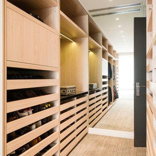 Foto de armario vestidor unisex, moderno, de tamaño medio, con puertas de armario de madera clara y moqueta