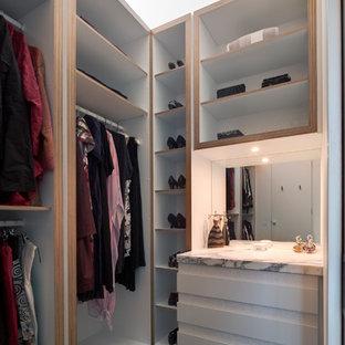 Diseño de armario vestidor de mujer, contemporáneo, pequeño, con armarios con paneles lisos, puertas de armario blancas y suelo de cemento