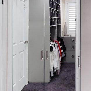 Ejemplo de vestidor unisex, minimalista, de tamaño medio, con armarios con paneles lisos, puertas de armario grises y moqueta