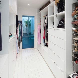 Réalisation d'un dressing design de taille moyenne et neutre avec un sol en bois peint, des portes de placard blanches, un placard à porte plane et un sol blanc.
