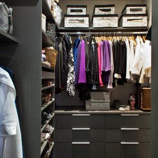 Modelo de armario vestidor de mujer, actual, pequeño, con armarios con paneles lisos, puertas de armario de madera en tonos medios, suelo de baldosas de porcelana y suelo negro
