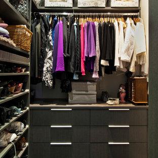 Ispirazione per una piccola cabina armadio per donna design con ante lisce, ante in legno bruno, pavimento in gres porcellanato e pavimento nero