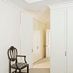Modelo de armario unisex, tradicional renovado, de tamaño medio, con armarios con paneles empotrados, puertas de armario blancas y moqueta