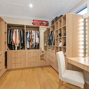 Mid-sized contemporary gender-neutral walk-in wardrobe in Brisbane with light wood cabinets, bamboo floors, flat-panel cabinets and beige floor.