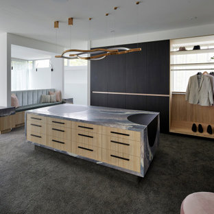 This is an example of a large contemporary gender-neutral walk-in wardrobe in Melbourne with black cabinets, carpet, grey floor and flat-panel cabinets.