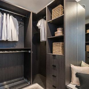 Contemporary gender-neutral walk-in wardrobe in Brisbane with flat-panel cabinets, dark wood cabinets, dark hardwood floors and beige floor.