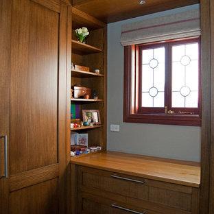 Idée de décoration pour un petit dressing victorien neutre avec un placard à porte shaker, des portes de placard en bois brun et moquette.