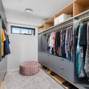 Ejemplo de armario vestidor unisex, actual, pequeño, con armarios con paneles lisos, puertas de armario grises, moqueta y suelo gris