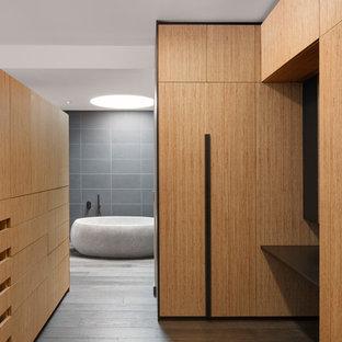 Diseño de vestidor unisex, contemporáneo, extra grande, con armarios con paneles lisos, puertas de armario de madera oscura, suelo de madera oscura y suelo marrón