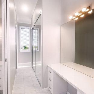 Kleines, Neutrales Ankleidezimmer mit Einbauschrank, flächenbündigen Schrankfronten, weißen Schränken, Keramikboden und weißem Boden in Sonstige
