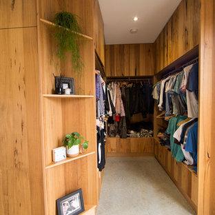 Ispirazione per una grande cabina armadio design con ante in legno scuro, pavimento in cemento e pavimento grigio