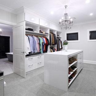 Foto di un'ampia cabina armadio unisex design con ante lisce, ante bianche, moquette e pavimento grigio