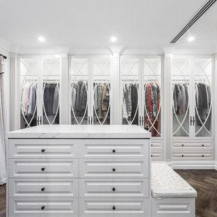 Diseño de armario vestidor actual, grande, con armarios tipo vitrina, puertas de armario blancas y suelo de madera oscura
