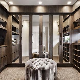 Imagen de vestidor unisex, contemporáneo, con armarios con paneles lisos, puertas de armario de madera en tonos medios, moqueta y suelo beige