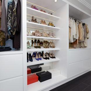 Idee per una grande cabina armadio per donna contemporanea con ante bianche e pavimento in gres porcellanato