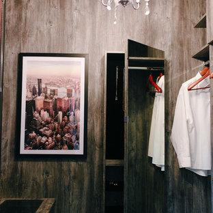 Ejemplo de armario vestidor unisex, moderno, de tamaño medio, con armarios abiertos, puertas de armario de madera oscura y suelo de baldosas de terracota
