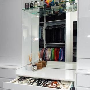 Immagine di un'ampia cabina armadio unisex minimalista con ante lisce, ante bianche, moquette e pavimento grigio