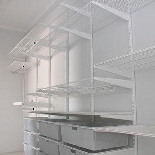 Modelo de armario vestidor unisex, de tamaño medio, con armarios abiertos, puertas de armario blancas y suelo de baldosas de porcelana