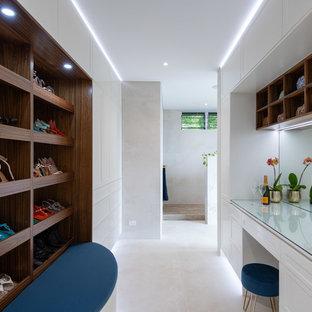 Imagen de armario vestidor unisex, contemporáneo, grande, con armarios estilo shaker, puertas de armario amarillas, suelo de baldosas de porcelana y suelo beige