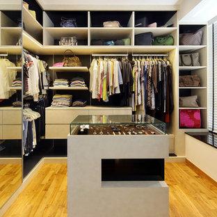 Modelo de armario vestidor unisex, actual, con puertas de armario blancas, suelo de madera en tonos medios y suelo beige