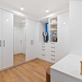 Large contemporary gender-neutral dressing room in Perth with flat-panel cabinets, white cabinets, medium hardwood floors and beige floor.