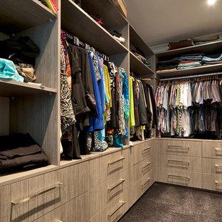 Modelo de armario vestidor unisex, minimalista, grande, con armarios con paneles lisos, puertas de armario de madera clara y moqueta
