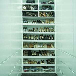 Foto de armario vestidor unisex, minimalista, de tamaño medio, con armarios con paneles lisos, puertas de armario blancas y moqueta