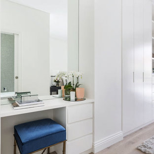 Contemporary gender-neutral storage and wardrobe in Sydney with flat-panel cabinets, white cabinets, light hardwood floors and beige floor.