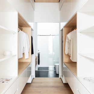 This is an example of a contemporary gender-neutral dressing room in Sydney with flat-panel cabinets, white cabinets, light hardwood floors and beige floor.